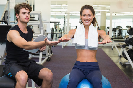 Trainer watching client sitting on exercise ball at the gym photo