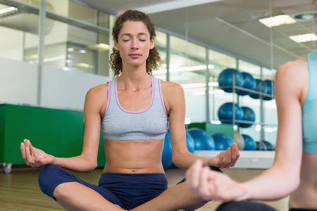 fit women: Fit women doing yoga together in studio at the gym