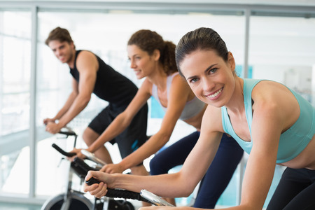 Fit people in a spin class with brunette smiling at camera at the gym photo