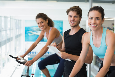 Fit women in a spin class with trainer taking notes and smiling at camera at the gym photo