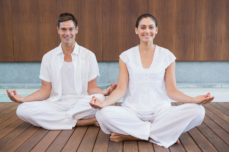 Attractive couple in white sitting in lotus pose smiling at camera in health spa photo