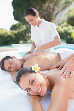 Attractive couple enjoying couples massage poolside outside at the spa photo