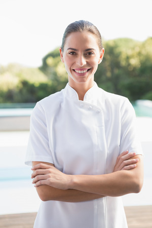 Smiling beauty therapist looking at camera outside at the spa Stock Photo