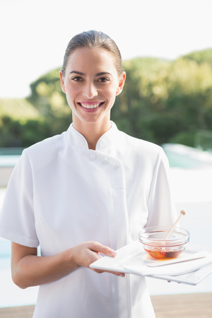 Smiling beauty therapist looking at camera holding plate with honey outside at the spa