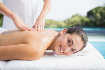 Happy brunette getting a massage poolside outside at the spa photo