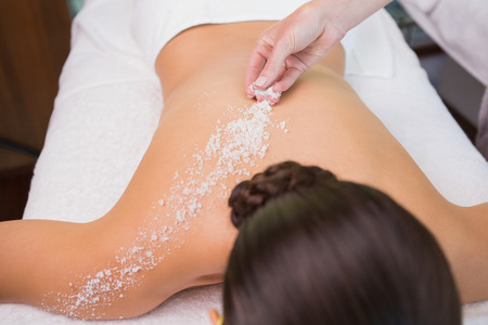 body scrub: Beauty therapist pouring salt scrub on womans back in the health spa