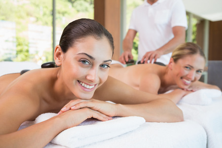 Pretty friends lying on massage tables with hot stones on\ their backs in the health spa