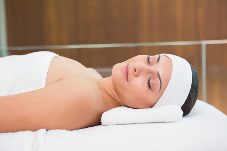 massage table: Peaceful brunette lying on massage table in the health spa Stock Photo