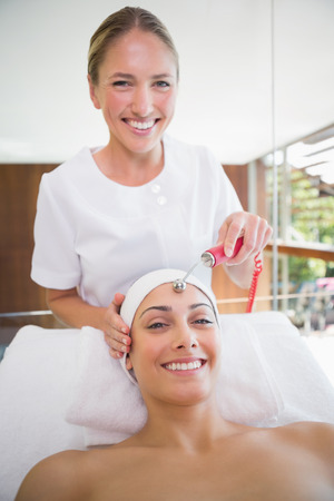 Smiling brunette getting micro dermabrasion in the health spa photo