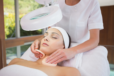 Peaceful brunette getting facial from beauty therapist in the health spa photo