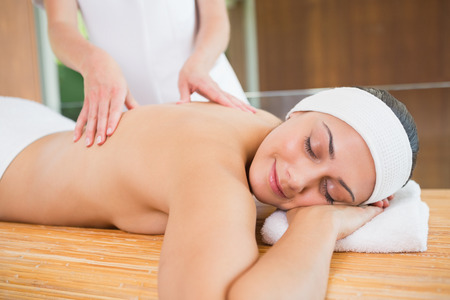 Peaceful woman getting a back massage in the health spa