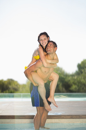 Gorgeous couple having fun poolside on holidays on a sunny day photo