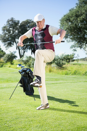 Angry golfer trying to break his club on a sunny day at the golf course photo