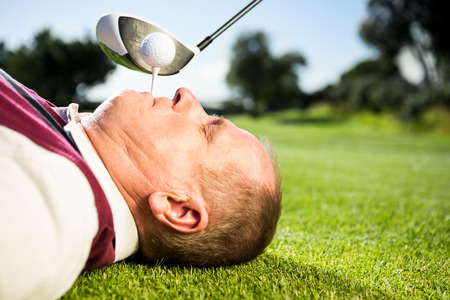 Golfer holding tee in his teeth on a sunny day at the golf course photo