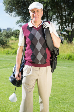 Golfer carrying his golf bag smiling at camera on a sunny day at the golf course photo