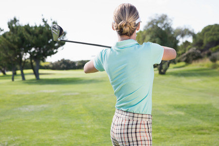 Female golfer taking a shot on a sunny day at the golf course photo