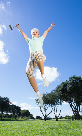 Female golfer leaping and cheering on a sunny day at the golf course Stock Photo