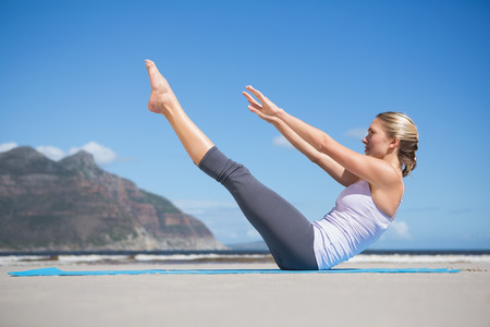 beach mat: Focused fit blonde doing yoga on the beach on a sunny day Stock Photo