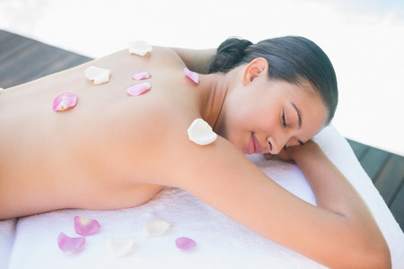 Smiling brunette lying on towel with rose petals outside at the spa photo