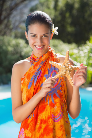 Smiling brunette in sarong showing starfish to camera outside at the spa Stock Photo
