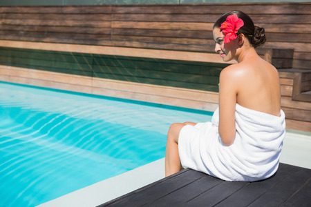 hair wrapped up: Beautiful brunette in towel sitting by the pool outside at the spa Stock Photo