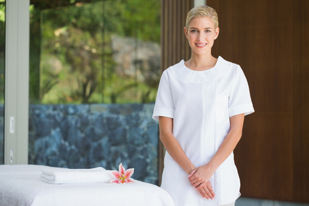 beauty therapist: Smiling beauty therapist standing beside massage towel at the spa