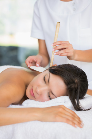 Relaxed brunette getting an ear candling treatment at the spa photo