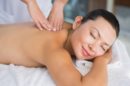 massage table: Content brunette getting a back massage at the spa