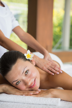 Brunette enjoying a peaceful massage smiling at camera at the\ health spa