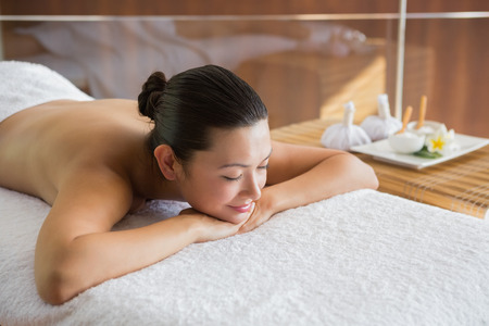 massage table: Content brunette relaxing on massage table at the health spa