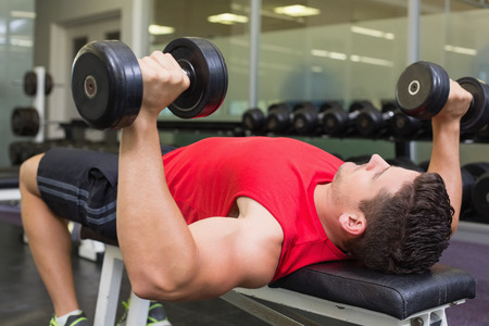 Bodybuilder lying on bench lifting dumbbells at the gym photo