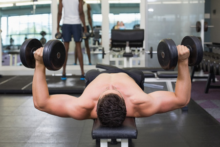 Shirtless bodybuilder lying on bench lifting heavy dumbbells at the gym