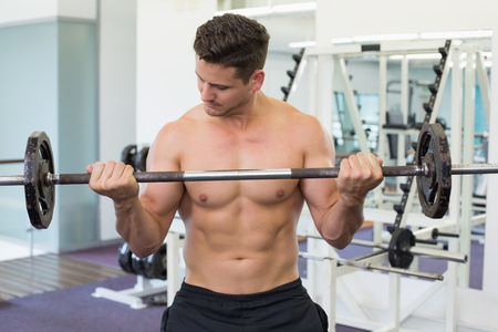 Shirtless bodybuilder lifting heavy barbell weight at the gym photo
