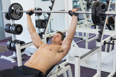 wincing: Shirtless bodybuilder lifting heavy barbell weight lying on bench at the gym Stock Photo