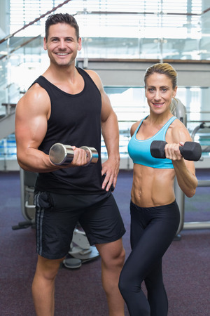 Bodybuilding man and woman holding dumbbells smiling at camera at the gym photo