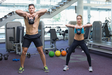 Bodybuilding man and woman lifting kettlebells at the gym photo
