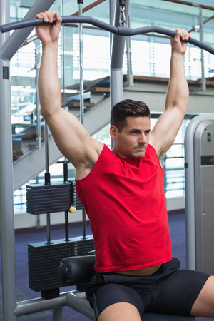 weight machine: Handsome bodybuilder using weight machine for arms at the gymer