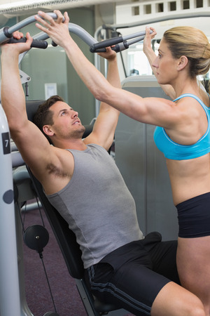 weight machine: Personal trainer coaching bodybuilder using weight machine at the gym Stock Photo