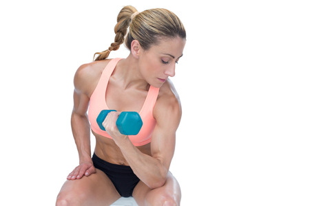 Strong woman doing bicep curl with blue dumbbell on white background photo