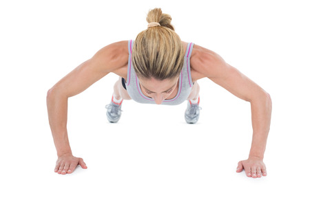 plank position: Strong woman doing press ups on white background