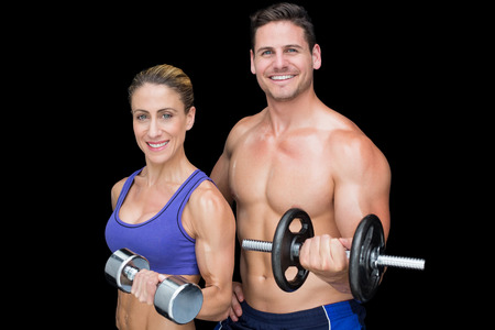 Crossfit couple posing with dumbbells smiling at camera on black background photo