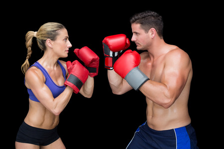 Bodybuilding couple posing with boxing gloves on black background Stock Photo