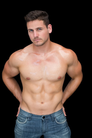 Muscular man posing in blue jeans on black background