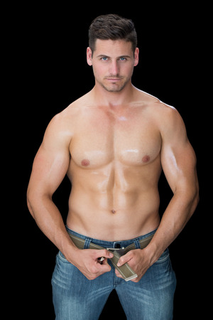 undoing: Muscular man posing in blue jeans on black background