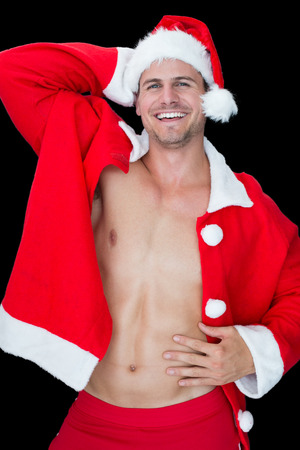 sexy santa: Smiling muscular man posing in sexy santa outfit on black background