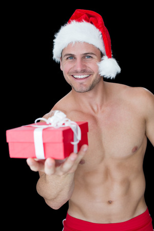 Smiling muscular man posing in sexy santa outfit offering gift on black background photo