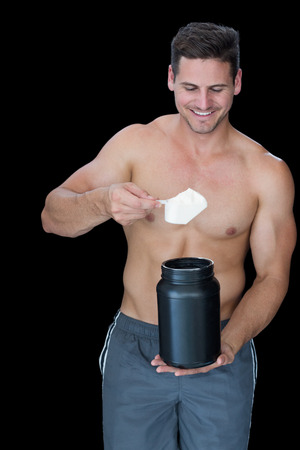 Happy muscular man scooping up protein powder on black background photo
