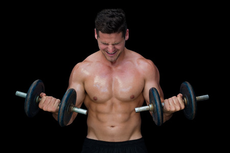 Strong crossfitter lifting up heavy black dumbbells on black background photo
