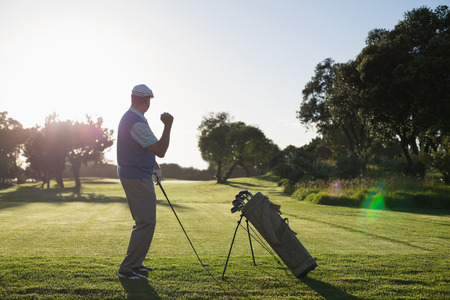Golfer happy with his shot on a sunny day at the golf course photo