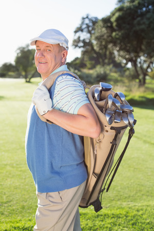Golfer standing holding his golf bag smiling at camera on a sunny day at the golf course photo